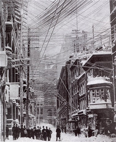 Figure 1 - New York City during the Great Blizzard of 1888, showing the tangle of electrical wires taking the strain of the snow.  After the disaster of the storm New York City began the task of placing electrical utilities below ground.  From the Wikicommons and in the public domain.