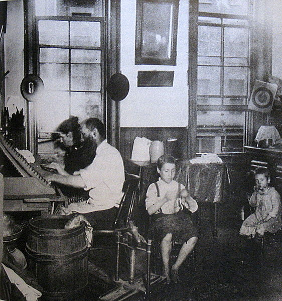"Figure 1 - Jacob Riis, ""Bohemian Cigar Makers at work in their tenement, 1914"" from the Wikimedia Commons and in the public domain."