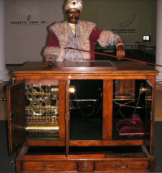 "Figure 1 - A replica of the ""The Turk,"" a fraudulent eighteenth century chess playing machine.  From the Wikimedia Commons originally uploladed by Carafe and in the public domain under creative commons license."
