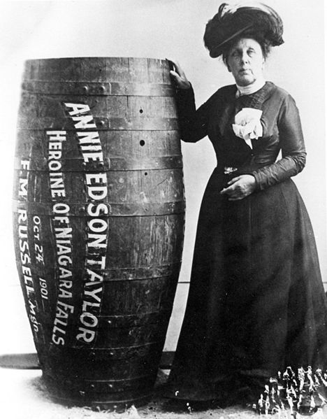 Figure 1 - Annie Edson Taylor and the barrell in which she became the first person to survive a plunge in a barrell over Niagra Falls, October 24, 1901. Image originally from the Francis J. Petrie Photograph Collection  Author, from the Wikimedia Commons and in the public domain.