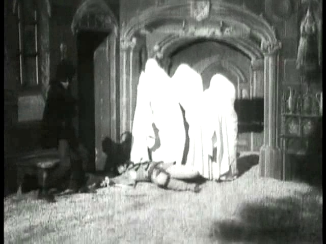 """Figure 1 - scene from the world's first """"horror movie, """"Le Manoir du Diable,"""" or """"The Manor of the Devil,"""" 1896.  It was a three-minute-long film, released on Christmas Eve, 1896, at the Theatre Robert Houdin, 8 boulevard des Italiens, Paris.  Here a gentleman is subdues by spectres.  From the Wikimedia Commons and in the public domain."""