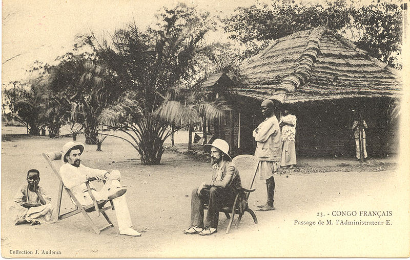 """Figure 1 - Postcard produced: [ca. 1905] Summary: Translated caption reads: """"French Congo. Passage of Mr. Administrator E. In the foreground, two leaders sitting in reclining chairs, in the background, village people and cabins. Congo Français. Photograph by J. Audema. General. In the public domain in the United States because of age."""